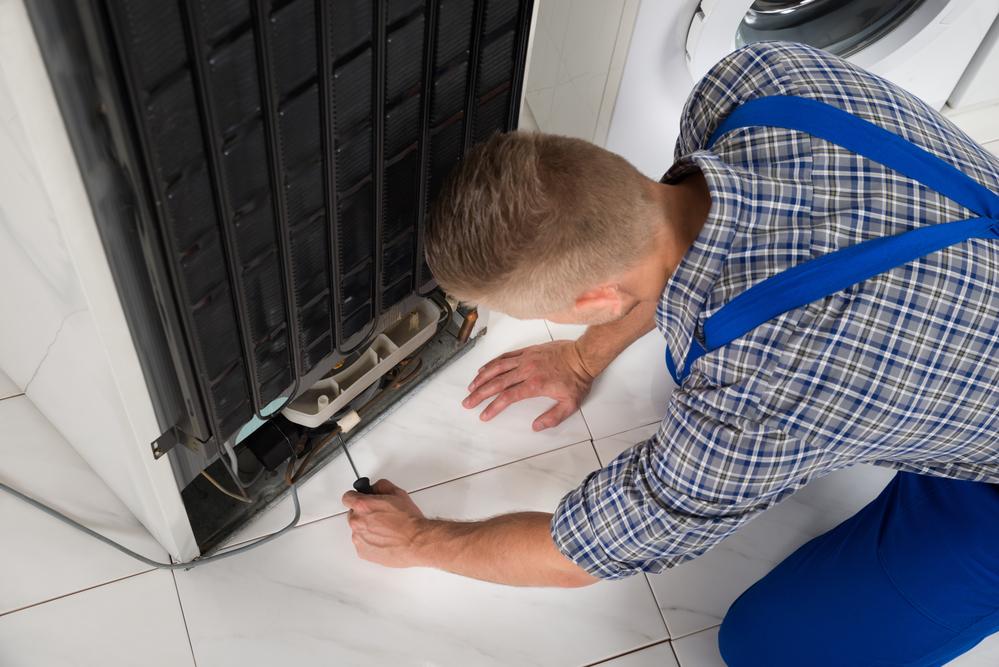 Appliance Allstars repairman works on appliance repair Fayetteville GA 30214 30215