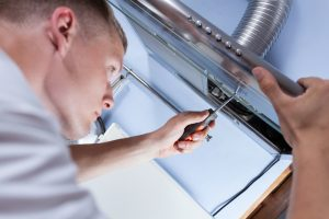 Appliance Repair Ellenwood GA - Appliance Allstars repairman fixing a kitchen extractor with a screwdriver