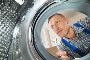 Repairman With wrench Looking Inside The Washing Machine